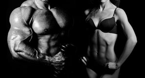 Bodybuilding. Man and woman. Bodybuilding. Strong men and a women posing on a black background stock photos