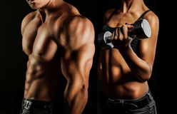 Bodybuilding. Man and  woman. Bodybuilding. Strong man and a woman posing on a black background Stock Photos