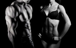 Bodybuilding. Man and woman. Bodybuilding. Strong man and a woman posing on a black background stock images