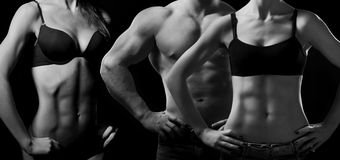 Bodybuilding. Man and  woman. Bodybuilding. Strong man and a woman posing on a black background Stock Image