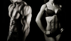 Bodybuilding. Man and woman. Bodybuilding. Strong man and a woman posing on a black background royalty free stock image