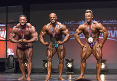 Bodybuilding Medalists Pose Together. Stellar male bodybuilders Zane Watson (2nd place) Alejandro Cambronero (1st) and Kim Jun Ho (3rd) match poses after being Royalty Free Stock Photo