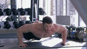 Bodybuilding, mięśniowa atleta z pięknym sporta ciałem robi pushups podczas władza treningu przy centrum sportowym zdjęcie wideo