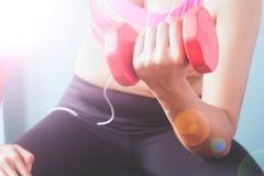 bodybuilding Mulher forte do ajuste no sutiã cor-de-rosa do esporte que exercita com peso vermelho Imagem de Stock