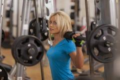 bodybuilding Mulher forte do ajuste que exercita com barbell menina que levanta peso no gym Imagem de Stock