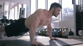 Bodybuilding, muscular athlete man with beautiful sports body does pushups during strength workout at gym stock video