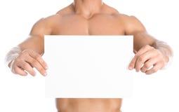 Bodybuilding och advertizing: en trevlig stark kroppsbyggare som rymmer ett pappers- vitt tomt kort isolerat på vit bakgrund i st royaltyfria foton