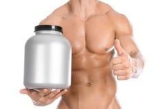 Bodybuilding- och sporttema: den stiliga starka kroppsbyggaren som rymmer en plast- krus med ett torrt protein och visar gest, is arkivbild