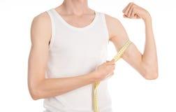 Bodybuilding- och sporttema: en tunn man i en vit T-tröja och jeans med att mäta bandet som isoleras på en vit bakgrund i studi Arkivbild