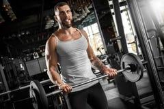 bodybuilding Posição farpada do homem no barbell de levantamento do gym motivado fotografia de stock royalty free