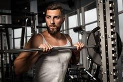 bodybuilding Posição farpada do homem no gym com o barbell que olha de lado curioso fotos de stock royalty free