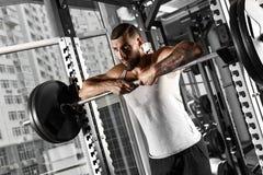 bodybuilding Posição farpada do homem que inclina-se no barbell no gym que olha para a frente sassy imagens de stock royalty free