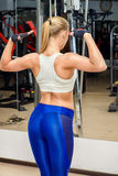 Bodybuilding. Slender young woman with an athletic physique standing back. Fitness sports. Bodybuilding Royalty Free Stock Photo
