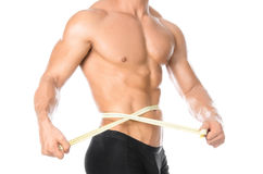Bodybuilding and Sports theme: handsome strong bodybuilder holding centimeter tape to measure body isolated on white background in Royalty Free Stock Photography