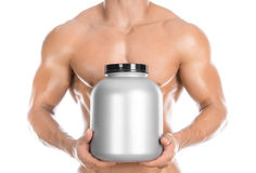 Bodybuilding and Sports theme: handsome strong bodybuilder holding a plastic jar with a dry protein and showing gesture isolated o Royalty Free Stock Photography