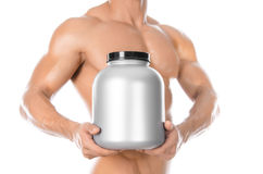 Bodybuilding and Sports theme: handsome strong bodybuilder holding a plastic jar with a dry protein and showing gesture isolated o. N white background Royalty Free Stock Photo