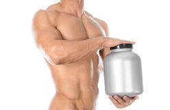 Bodybuilding and Sports theme: handsome strong bodybuilder holding a plastic jar with a dry protein and showing gesture isolated o Stock Photo