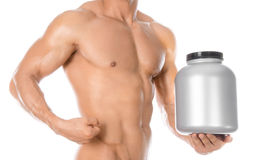 Bodybuilding and Sports theme: handsome strong bodybuilder holding a plastic jar with a dry protein and showing gesture isolated o Stock Photos