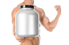 Bodybuilding and Sports theme: handsome strong bodybuilder holding a plastic jar with a dry protein and showing gesture isolated o Royalty Free Stock Image