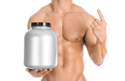 Bodybuilding and Sports theme: handsome strong bodybuilder holding a plastic jar with a dry protein and showing gesture isolated o. N white background Royalty Free Stock Images