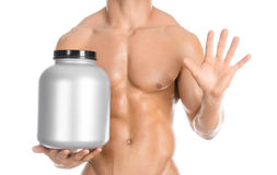 Bodybuilding and Sports theme: handsome strong bodybuilder holding a plastic jar with a dry protein and showing gesture isolated o Stock Photography