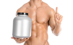 Bodybuilding and Sports theme: handsome strong bodybuilder holding a plastic jar with a dry protein and showing gesture isolated o. N white background Royalty Free Stock Photography