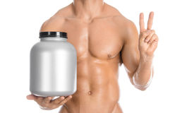 Bodybuilding and Sports theme: handsome strong bodybuilder holding a plastic jar with a dry protein and showing gesture isolated o. N white background Stock Image