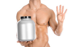 Bodybuilding and Sports theme: handsome strong bodybuilder holding a plastic jar with a dry protein and showing gesture isolated o. N white background Royalty Free Stock Image