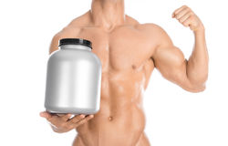 Bodybuilding and Sports theme: handsome strong bodybuilder holding a plastic jar with a dry protein and showing gesture isolated o. N white background Stock Photo