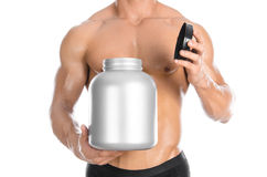 Bodybuilding and Sports theme: handsome strong bodybuilder holding a plastic jar with a dry protein and showing gesture isolated o Stock Images