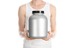 Bodybuilding and Sports theme: a thin man in a white T-shirt and jeans holding a plastic jar with a protein isolated on a white ba. Ckground Royalty Free Stock Photos