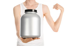 Bodybuilding and Sports theme: a thin man in a white T-shirt and jeans holding a plastic jar with a protein isolated on a white ba royalty free stock photo