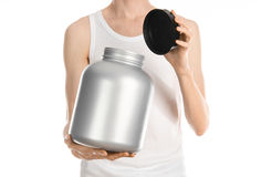 Bodybuilding and Sports theme: a thin man in a white T-shirt and jeans holding a plastic jar with a protein isolated on a white ba Stock Photo