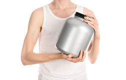 Bodybuilding and Sports theme: a thin man in a white T-shirt and jeans holding a plastic jar with a protein isolated on a white ba Stock Image
