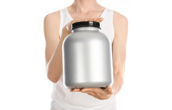 Bodybuilding and Sports theme: a thin man in a white T-shirt and jeans holding a plastic jar with a protein isolated on a white ba Royalty Free Stock Photos