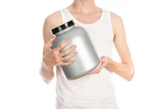 Bodybuilding and Sports theme: a thin man in a white T-shirt and jeans holding a plastic jar with a protein isolated on a white ba. Ckground Royalty Free Stock Image