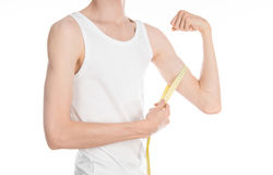 Bodybuilding and Sports theme: a thin man in a white T-shirt and jeans with measuring tape isolated on a white background in studi Stock Photo