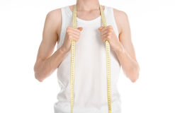 Bodybuilding and Sports theme: a thin man in a white T-shirt and jeans with measuring tape isolated on a white background in studi Royalty Free Stock Photography