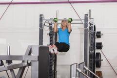 bodybuilding Starke Sitzfrau, die in einer Turnhalle - Handeln von ZugUPS trainiert Lizenzfreie Stockfotografie
