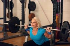 bodybuilding Starke Sitzfrau, die mit Barbell trainiert Mädchen, das Hocken mit großen Gewichten tut Lizenzfreie Stockfotos