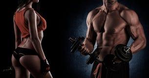 bodybuilding Starker Mann und eine Frau, die auf einem schwarzen backgroun aufwirft Lizenzfreies Stockfoto