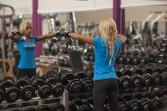 bodybuilding Sterke geschikte vrouw die met domoren uitoefenen meisje het opheffen gewichten in gymnastiek royalty-vrije stock fotografie