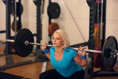 Bodybuilding. Strong fit woman exercising with barbell. girl doing squats with big weights. Royalty Free Stock Photos