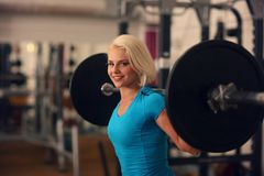 Bodybuilding. Strong fit woman exercising with barbell. girl doing squats with big weights. Smile and look to camera with barbell on shoulders Royalty Free Stock Image