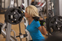 Bodybuilding. Strong fit woman exercising with barbell. girl lifting weights in gym Royalty Free Stock Image