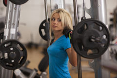 Bodybuilding. Strong fit woman exercising with barbell. girl lifting weights in gym Royalty Free Stock Photos