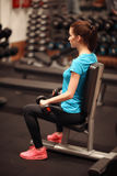 Bodybuilding. Strong fit woman exercising with dumbbells. Muscular girl lifting weights in gym Stock Images