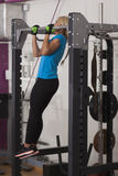 Bodybuilding. Strong fit woman exercising in a gym - doing pull-ups. Stock Images