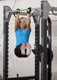 Bodybuilding. Strong fit woman exercising in a gym - doing pull-ups. Royalty Free Stock Photo