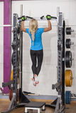 Bodybuilding. Strong fit woman exercising in a gym - doing pull-ups. Royalty Free Stock Image
